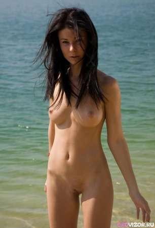 Красивая брюнетка фотографируется на пляже