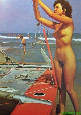 голая женщина настраивает парусник