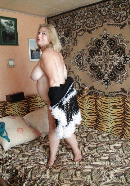 Зрелая толстушка эротично позирует на кровати