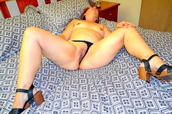 Зрелая женщина показывает себя на кровати