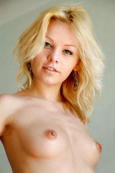 Худенькая блонда позирует в чулках и показывает узенькую кису