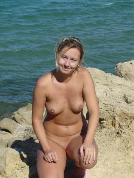 Жена на озере загорает голая