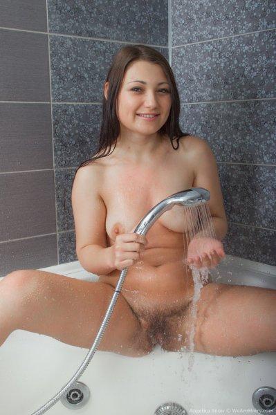 Фигуристая брюнетка обнажает круглую попку в ванной