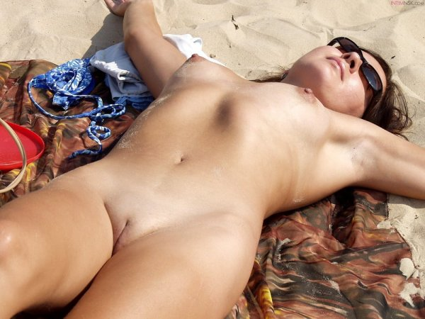 Молодые нудистки нежатся на пляже
