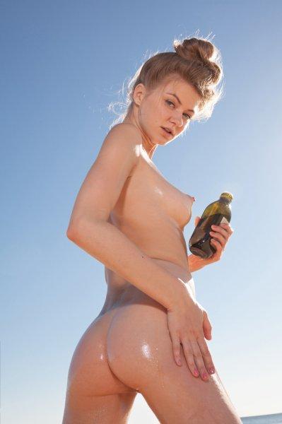 Голая цыпочка намазывается маслом на пляже