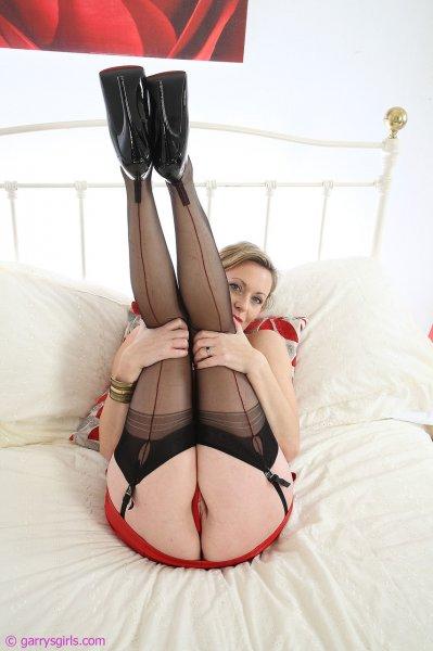 Шикарная зрелая милфа мастурбирует в чулках на кровати