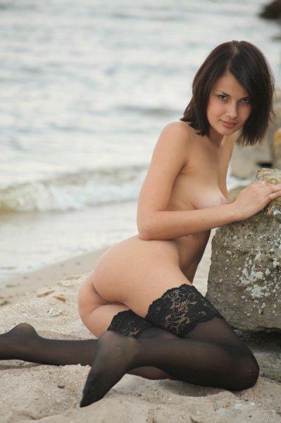 Темноволосая красотка позирует на пляже